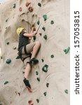 A Teen Boy Climbing On A Rock...