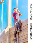 Small photo of Russia, Samara, June 2019: a beautiful sports girl, a participant in the race of heroes, overcomes a high wooden wall with the help of the Thick Rope. Text in Russian: race of heroes, platoon