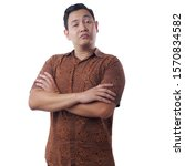 Small photo of Portrait of Asian man wearing batik shows arrogant cynical proud facial expression, standing with crossed arms isolated on white