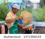 Small photo of Melaka, Malaysia- Circa November 2019; A Malay man char grilling chicken satay at his hawker's stall. Satay is a popular dish in Malaysia. Originated from Indonesia.