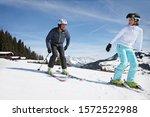 Couple Skiing On Slope At Ski...