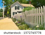 A white fence and colonial home on the historic town green in Lexington, MA