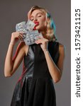 Blonde girl in black stylish dress holding and kissing some money, posing against gray background. Gambling entertainment, poker, casino. Close-up. - stock photo