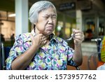 Small photo of Asian senior woman suffers from choke,clogged up food,elderly people choking during feeding,food might stuck in the throat and suffocate with sever pain injury,health problem, asphyxia,suffocation