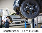 Small photo of Car repair in the service station. Hands of a mechanic in overalls repairing the car on the lift without wheel, holding the tire and mechanical works.