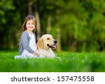 Stock photo little girl sitting on the grass with labrador retriever in the summer park 157475558