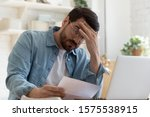 Small photo of Upset frustrated young man reading bad news in postal mail letter paper document sit at home table, depressed stressed guy worried about high bill tax invoice, overdue debt notification money problem
