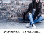 Small photo of Young woman in hood is sitting on skateboard and holding smoldering cigarette and bottle of beer. Homeless teenage girl is drinking and smoking in abandoned building. Dregs of society concept.