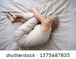 Small photo of View from top depressed middle-aged alone female curled up in fetal position lying in bed, concept of chronic insomnia, sleeping disorder, grieving about divorce or diagnosis disease, mental problems