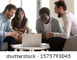 Small photo of Four different ethnicity colleagues asian african caucasian friendly company staff sitting together in office lounge on couch watching funny video during break, good relationships and amity concept