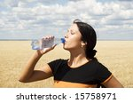 a young beautiful girl drinking water over sky background - stock photo
