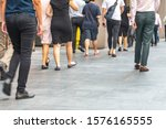 Small photo of Back view of action movement motion blur of unidentified people's lower legs walking hastily in busy city during daytime