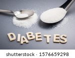 Small photo of Diabetes text with tablespoon and teaspoon of white sugar, amount of sugar necessary concept
