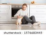 Man Feeding Cute Cat In Kitchen