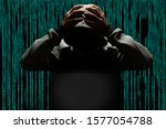 Computer hacker making a mistake, clutching his head in his hands, sitting in front of a computer - stock photo