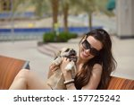Stock photo beautiful happy young woman in black dress with cute small dog puppy have fun on street 157725242