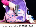 Small photo of Girl hides a gun in a school backpack. Covert carrying weapons for protection. Weapons at school, assault at school, shooting