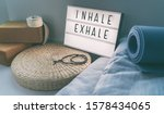 Small photo of Yoga breathing INHALE EXHALE sign at fitness class on lightbox inspirational message with exercise mat, mala beads, meditation pillow. Accessories for fit home lifestyle.