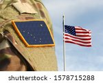 Flag of State of Alaska on military uniform and Flag of USA weaving in the sky.