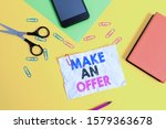 Small photo of Text sign showing Make An Offer. Conceptual photo Proposal Bring up Volunteer Proffer Bestow Bid Grant Paper sheets pencil clips smartphone scissors notebook colored background.