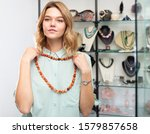 Small photo of Young interested woman trying on elegant necklace from red jasper in modern jewelry shop