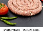 raw sausage on a black... | Shutterstock . vector #1580211808