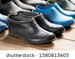 Small photo of Old rubber boots of a big family stand on the wooden floor. Short rubber country goloshes