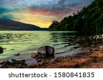 A very small boulder protrudes from the shallow shore of the lake under a twilight sky in Devil