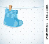 Baby boy shower card. Knitted socks on light background. Arrival card with place for your text.