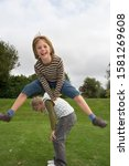 Small photo of Portrait of active boy playing leapfrog game with girl in park garden