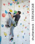 Small photo of A man climbs up on a climbing wall.