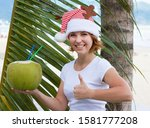Young woman is enjoying summer with coconut drink in her hands, thumb up gesture is cool. Happy girl on the background of the Malm in a red santa hat celebrates the holiday, merry christmas, new year.