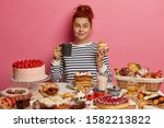 Small photo of Ginger girl sits at festive table overloaded with many sweet desserts, eats yummy freshed baked cake and drinks tea, has unhealthy but tasty lunch, feels hungry, being voluptuous. Confectionery