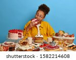 Small photo of Hungry greedy Afro American girl bites big delicious piece of cake, poses at table with many yummy desserts, has sweet breakfast at home, unhealthy nutrition, isolated over blue wall, gets pleasure