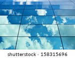 Blue cloudy sky reflection in the office building's windows composition - stock photo