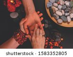 Small photo of Young fortune teller divines the hand of young man around candles and other magical paraphernalia. Divine magic and occultism concept. Divination. Top view, toned.