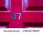 House Number 37 On A Dark Red...