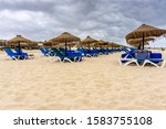 Rows Of Straw Parasols And...