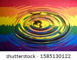 Circular ripples on a water surface reflecting the Gay Pride Extinction Rebellion flag and logo. Abstract Extinction Rebellion climate change background.