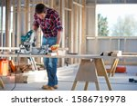 Carpenter using circular power saw to cut wood on indoor building construction site - stock photo
