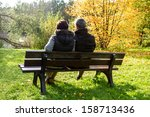 couple sitting on a park bench... | Shutterstock . vector #158713436