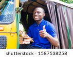 Small photo of young black african tricycle drive holding nigerian money given a thrumps up