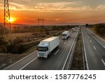 Small photo of Fleet of blue lorry trucks on a country highway under an amazing orange sunset sky