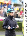 Small photo of MARKET RASEN RACECOURSE, LINCOLNSHIRE, UK : 28 September 2019 : An elegant race day female Steward with clip board and checks the racehorses from the Parade Ring at Market Rasen Races