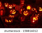 Stock photo group of candle lit halloween pumpkins in park on fall evening 158816012
