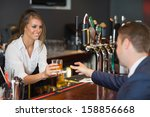 Small photo of Beautiful waitress serving handsome businessman in a classy bar