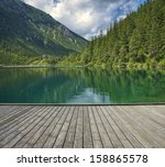 Empty Wooden Pier With Mountai...