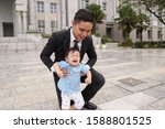 Small photo of Career asian man wearing smart work wear looking stressful with his adorable but cranky son, outside an office buidling in Putrajaya Malaysia.