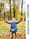 little girl tossing leaves in... | Shutterstock . vector #158931308