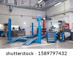 Small photo of Blue stand wheel alignment convergence of the car during regular maintenance in the workshop for repair of vehicles . Auto service industry.
